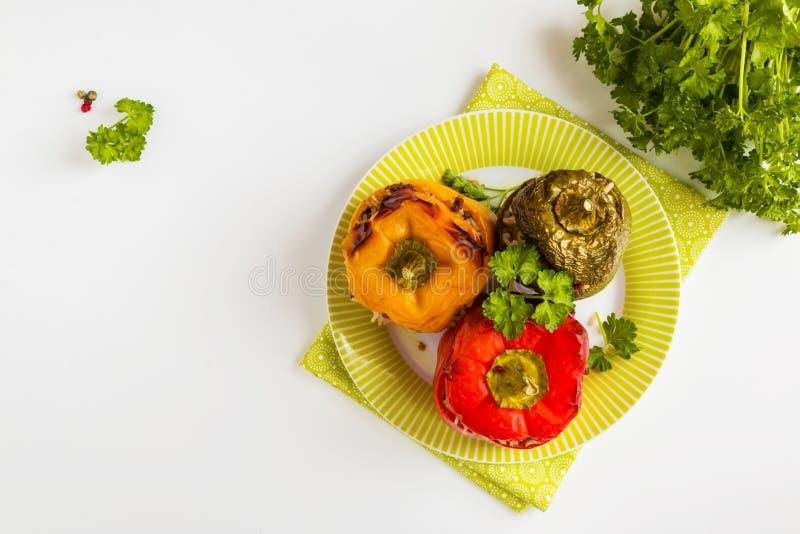 Bakade för guling, röda och gröna för spanska peppar, välfyllt med köttfärs och ris Ny persilja, vit tabell, bästa sikt arkivfoton
