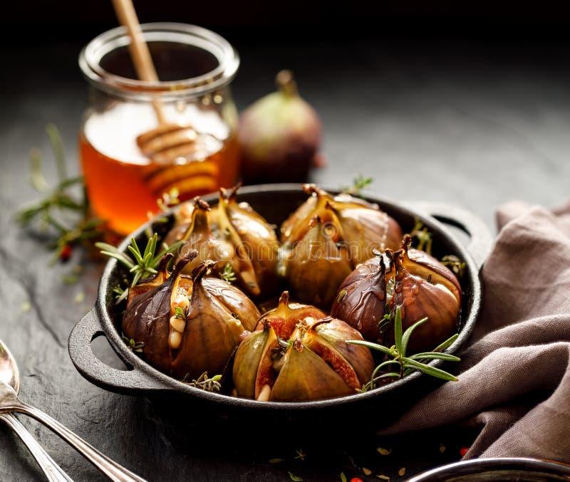 Bakade fikonträd som är välfyllda med gorgonzola ost, sörjer muttrar, honung och örter i en svart maträtt på ett mörker, stenbakg royaltyfri foto