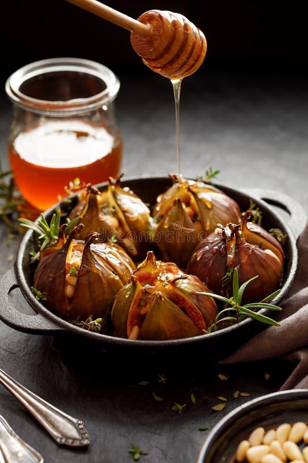 Bakade fikonträd som är välfyllda med gorgonzola ost, sörjer muttrar, honung och örter i en svart maträtt på ett mörker, stenbakg arkivfoto