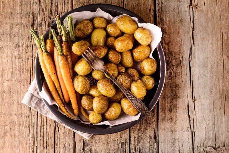 Bakade grönsaker grillade morötter, och potatisgrönsaker lagade mat på gallret som sund träbakgrund bantar mathorisontalkopian royaltyfria foton