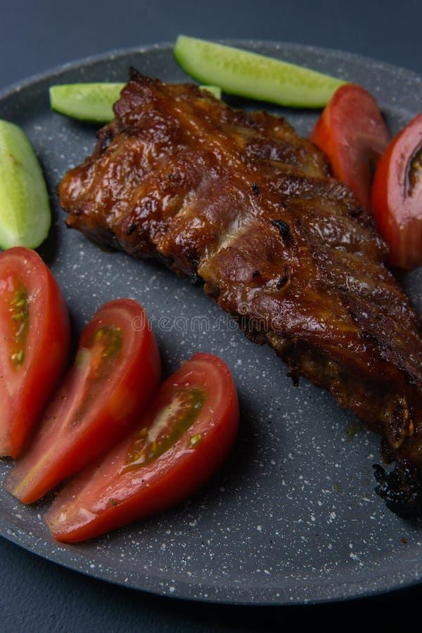 bakade grisköttstöd med honunglögn med nya skivade tomater och gurkor för ‹för †på ett mörkt - grå konkret tabletop royaltyfri fotografi