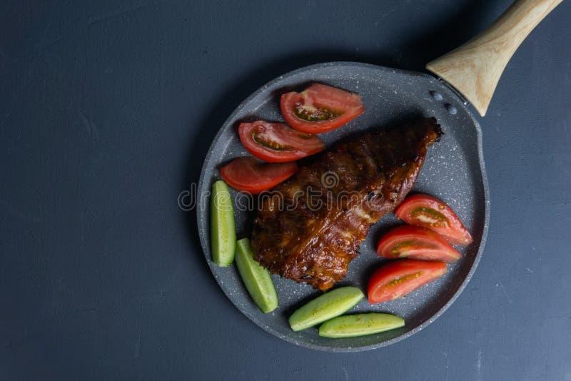 bakade grisköttstöd med honunglögn med nya skivade tomater och gurkor för ‹för †på ett mörkt - grå konkret tabletop royaltyfria foton