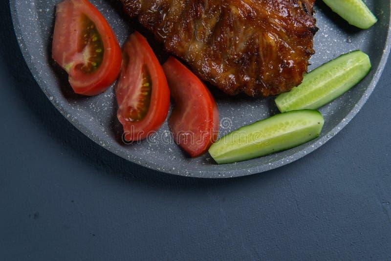 bakade grisköttstöd med honunglögn med nya skivade tomater och gurkor för ‹för †på ett mörkt - grå konkret tabletop arkivbilder