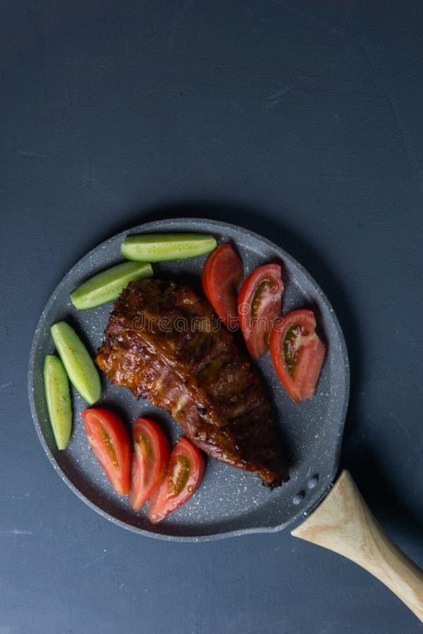 bakade grisköttstöd med honunglögn med nya skivade tomater och gurkor för ‹för †på ett mörkt - grå konkret tabletop arkivbild