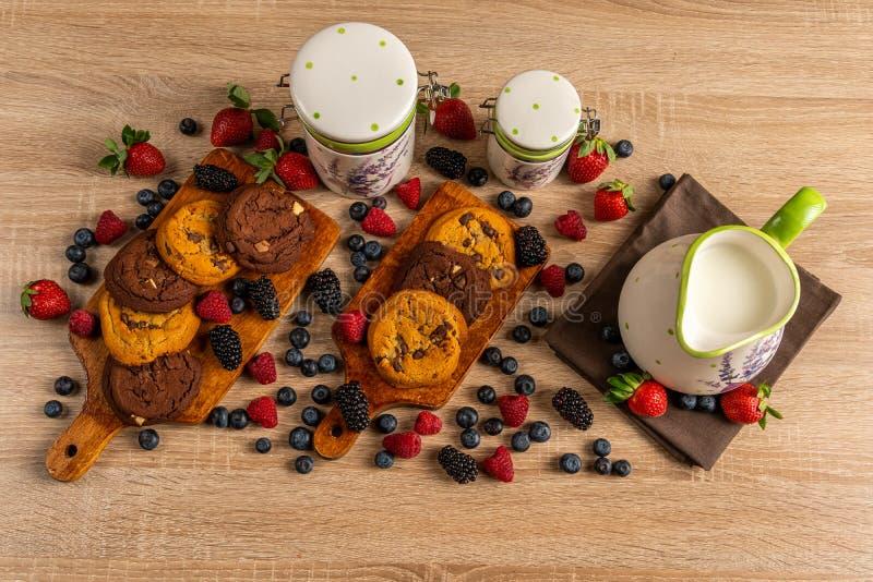 Bakade kakor med mjölkar i keramiska tillbringare- och skogfrukter på trätabellen royaltyfri foto