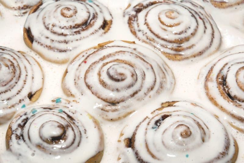 Bakade kanelbruna bullar hälldes över med en vit isläggning för att blöta royaltyfri fotografi