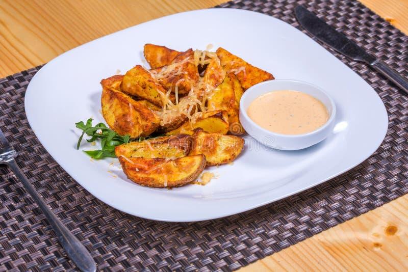 Bakade kryddiga potatisar med ost tjänade som efter sås och örter fotografering för bildbyråer