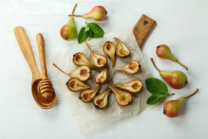 Bakade päron med honung på en träbakgrund royaltyfria foton