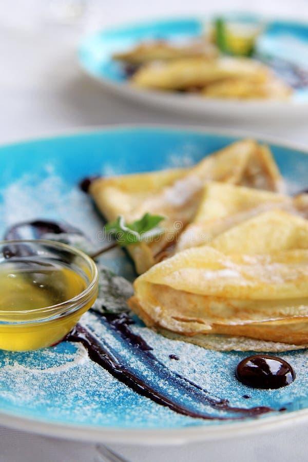 Bakade pannkakor med pudrad socker och sås för mintkaramell honung på blåttplattan royaltyfri fotografi
