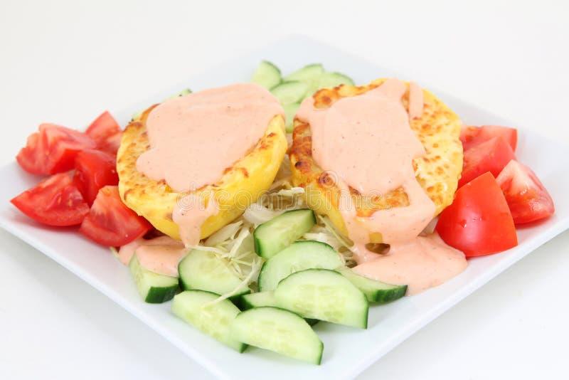 Bakade potatisar med sås och grönsaker royaltyfria bilder