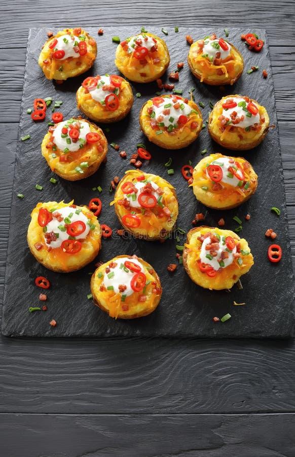 Bakade potatisar som laddas med grated ost royaltyfri foto
