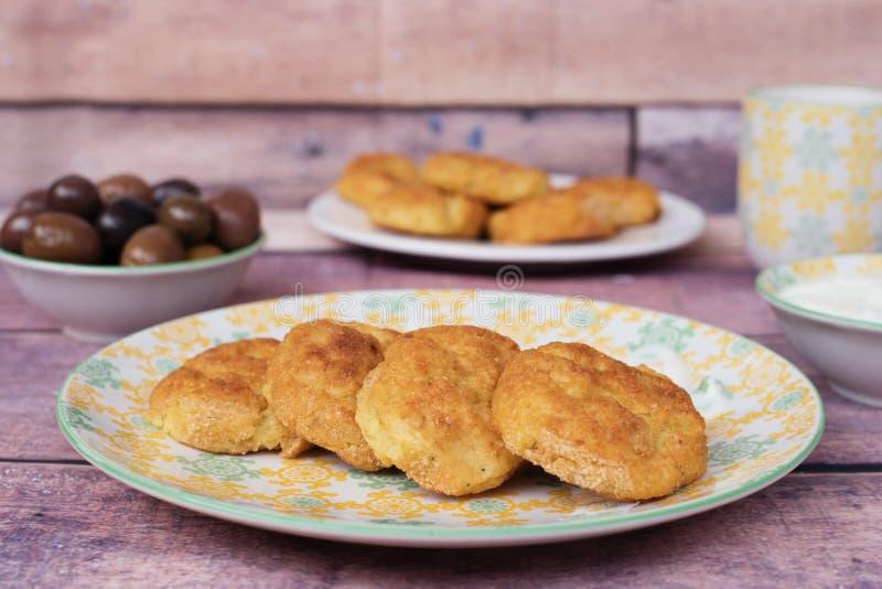 Bakade potatisköttbullar klumpa ihop sig i en gul platta Tillbaka oliv och yoghurtsås Closeup nya signaler Wood bakgrund arkivbilder
