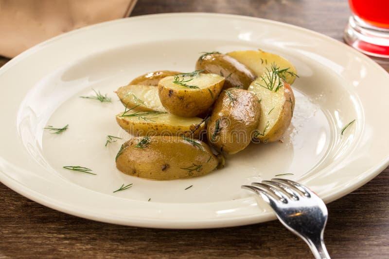 Bakade potatiskilar på den vita plattan på trätabellen arkivfoton