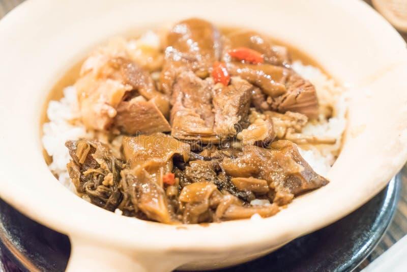 Bakade ris med kokt griskött lägger benen på ryggen i lerakruka royaltyfri bild