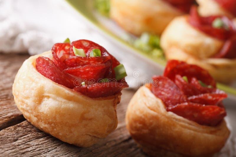 Bakade rullar med salami i form av rosmakro horisontal arkivfoton