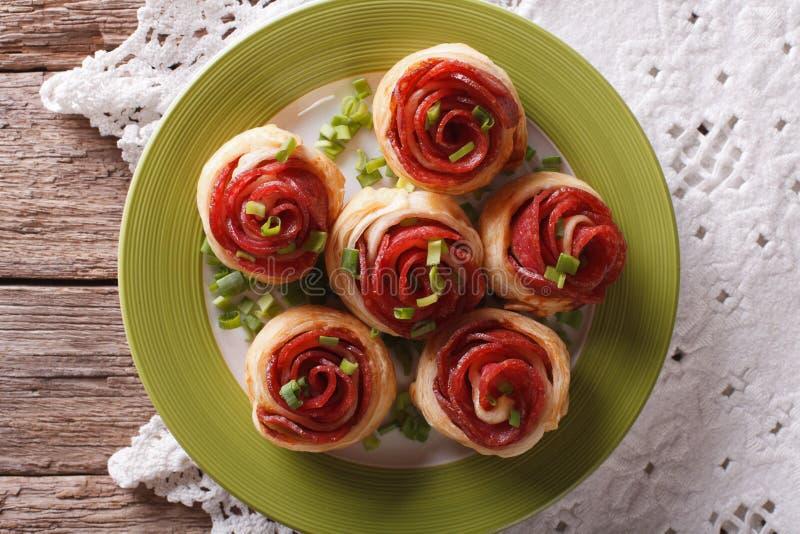 Bakade rullar med salami i form av rosnärbild horizonta arkivfoton