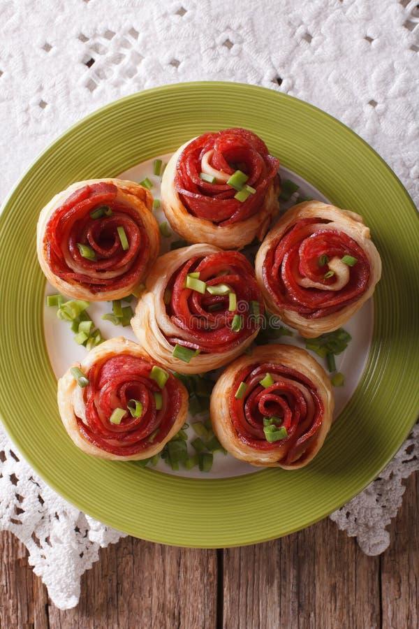 Bakade rullar med salami i form av rosnärbild vertikalt fotografering för bildbyråer