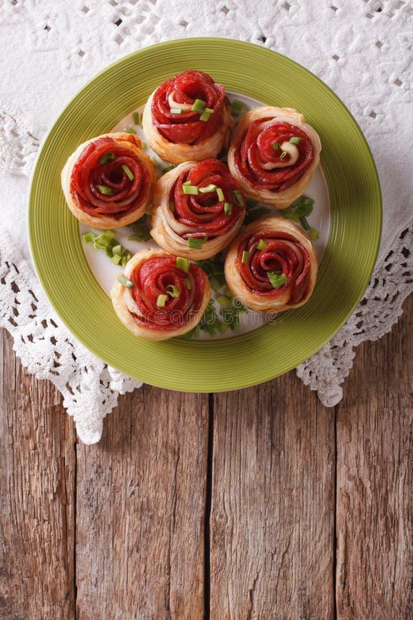 Bakade rullar med salami i form av rosor Vertikal bästa sikt arkivfoton