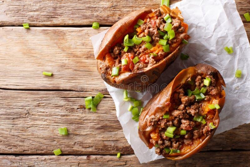 Bakade sötpotatisar som är välfyllda med jordnötkött med tomater och royaltyfria foton