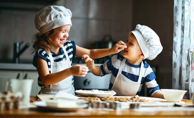 Bakar roliga ungar för lycklig familj kakor i kök arkivfoton