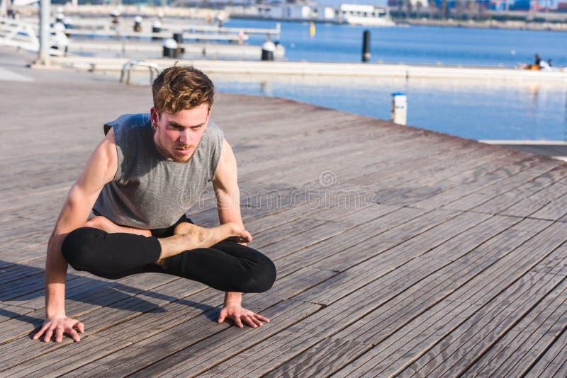Bakasana, yoga posture of an asana that balances the arms.  stock images