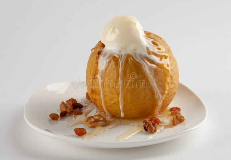 Bakat äpple med honung, glass och muttrar arkivbilder