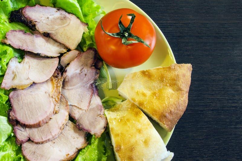 Bakat griskött med tomater arkivbilder