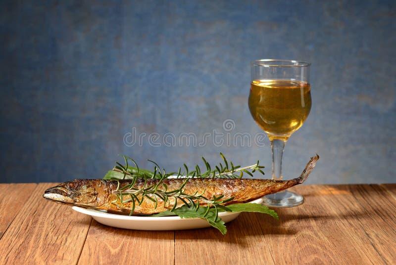 Bakat makrillfisk och vin i exponeringsglaset royaltyfri fotografi