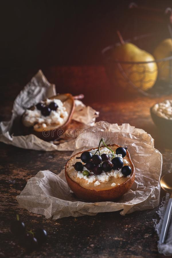 Bakat päron med honung, keso och vinbär Ny hemlagad efterrätt Matsammansättning i en låg tangent fotografering för bildbyråer