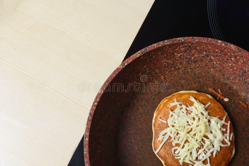 Bakat utan smörpannkakan i en panna som överst strilas med grated ost Stäng sig upp av smakligt frukostkopieringsutrymme arkivbilder
