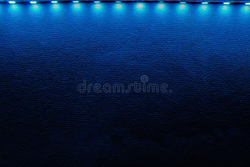 Bakbelyst bakgrund av blåa ledde lysrör och reflexioner på svart royaltyfri fotografi