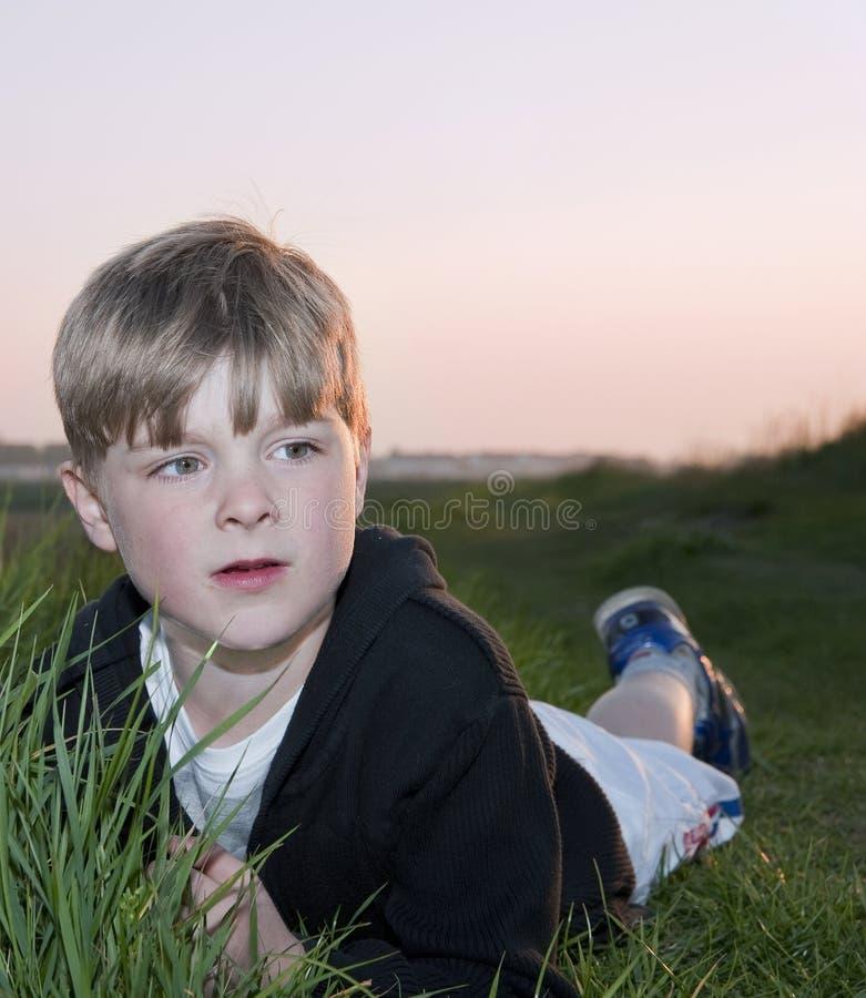 bakbelyst barn för pojkeståendesun fotografering för bildbyråer