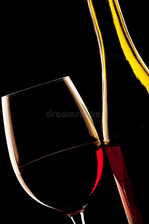 Bakbelyst detalj av ett exponeringsglas av rött vin och vinflaskan arkivbilder