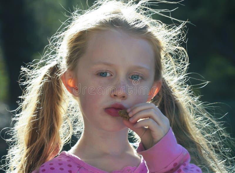 bakbelyst kaka som little äter flickahår royaltyfri bild