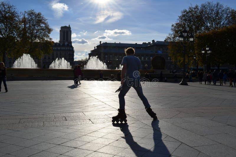 Bakbelyst kontur av ?ka skridskor f?r rulle f?r ung man ?vande i mitten av Paris arkivfoton