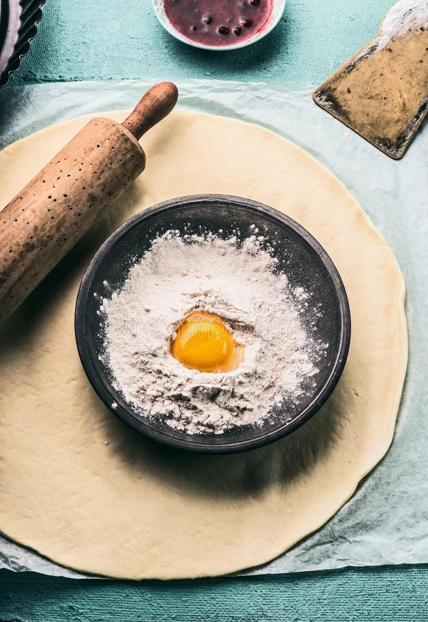 Bake concept. Dough, rolling pin and bowl with flour and egg. Top view stock images