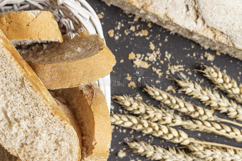Bake fresh bread in the village. Wheat ears and sliced bread on the table. Harvest of cereals. stock photos