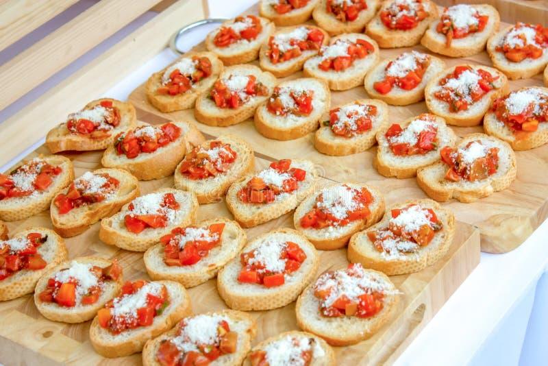 Baked在木屠户滑了法式面包被安排,冠上由乳酪和煮熟的蕃茄立方体 读服务 免版税库存图片