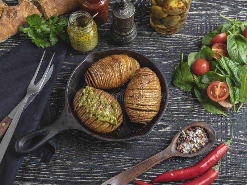 Baked在皮肤,沙拉整个烤了土豆 在桌上的生铁平底锅 免版税图库摄影