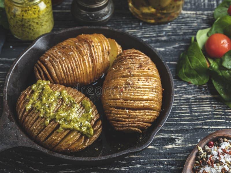 Baked在皮肤,沙拉整个烤了土豆 在桌上的生铁平底锅 图库摄影