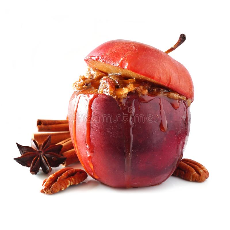 Baked apple with caramel, brown sugar and and nuts isolated on white royalty free stock photography