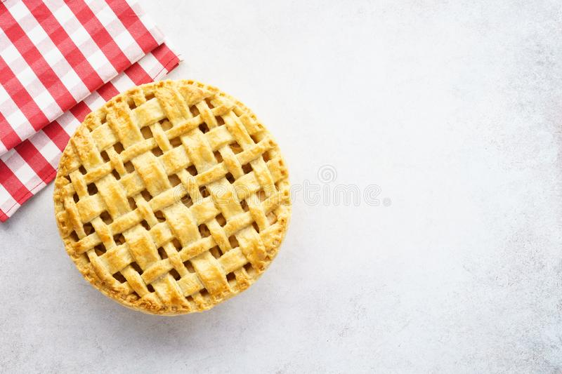 Baked apple pie and red checkered tablecloth on gray background. Baked apple pie and red checkered tablecloth on light gray background. Blank space for text stock photos