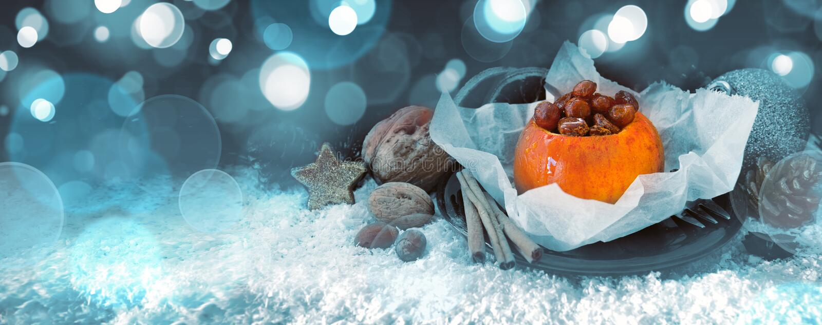 Baked apple with raisins and christmas decoration. stock photo