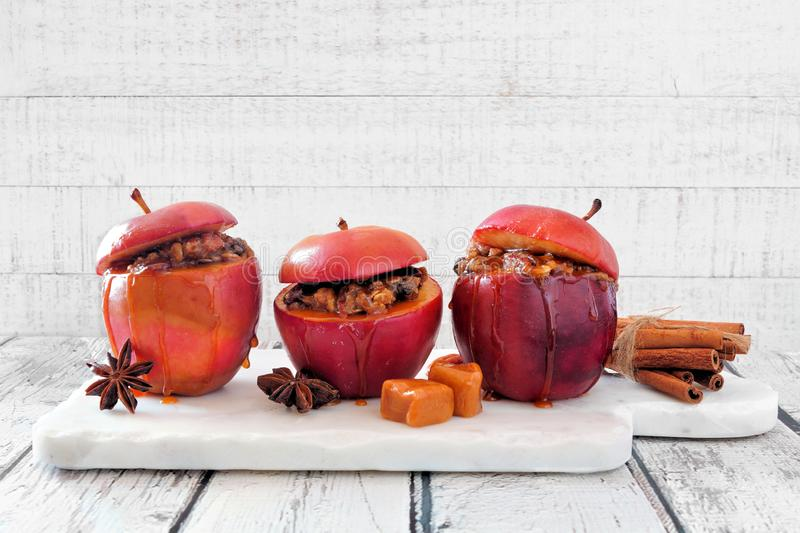 Baked apples with caramel, brown sugar and and nuts on a white wood background stock photo