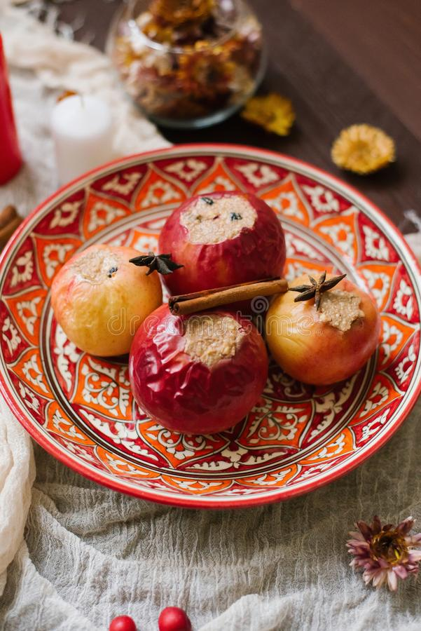 Baked apples with cottage cheese and cocoa on a beautiful red plate with a pattern on a brown wooden background royalty free stock photography