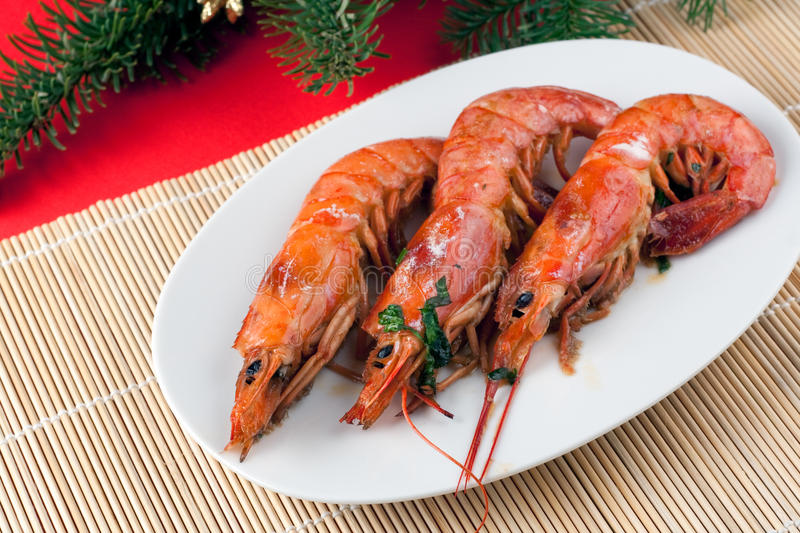 Baked Argentinian Prawns in White Wine. An elegant plate with Baked Argentinian Prawns in White Wine with Christmas decorations stock photography