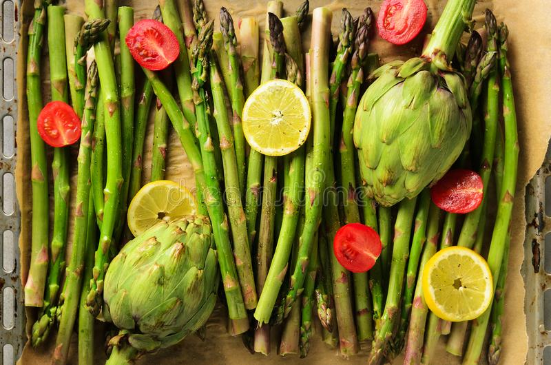 Baked asparagus, artichoke with lemon, tomatoes cherry, salt. Raw, vegan, vegetarian and clean eating concept. stock photography