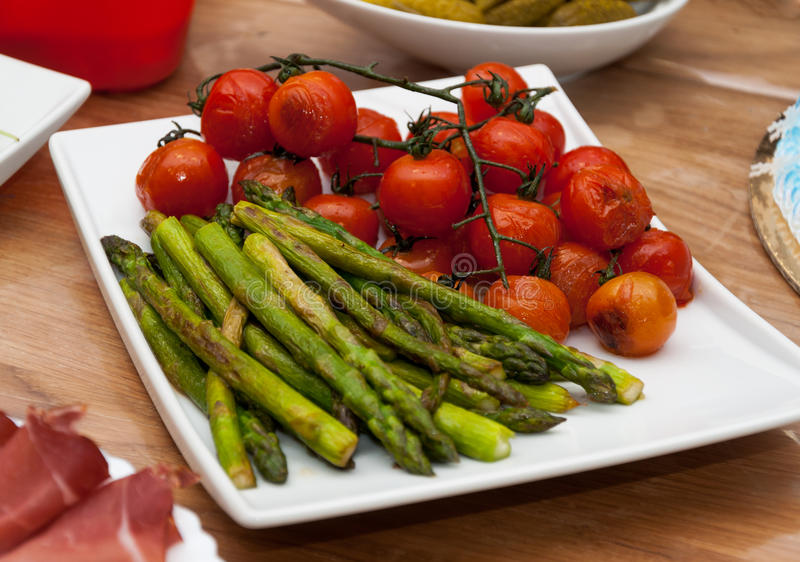 Baked asparagus and cherry tomato garnish royalty free stock photography