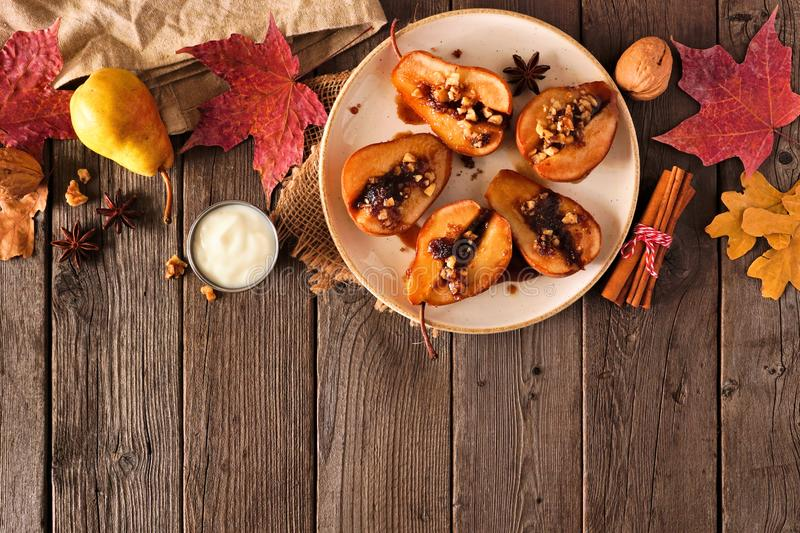 Sweet baked autumn pears, above view, top border on a rustic wood background stock photography