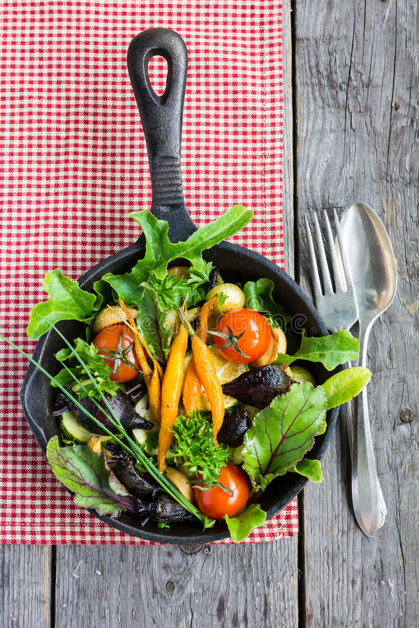 Baked baby carrots, beetroot, cherry tomatoes, pearl onion and garlic in a pan with fresh chard, salad leaves royalty free stock photos